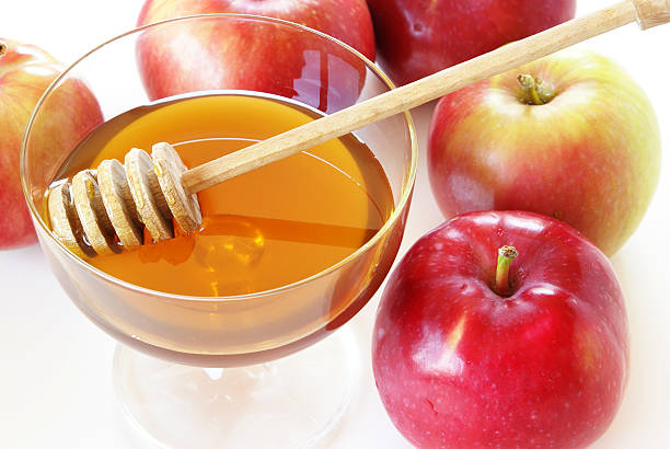 Cup of honey with stirrer and whole apples for Rosh Hashana